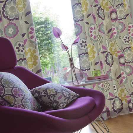 Clarke and Clarke -  Impressions Fabric Collection - Purple, grey and green bold printed floral curtains and cushions on purple armchair