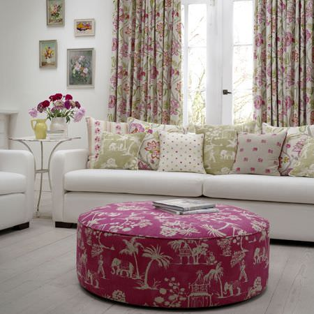Clarke and Clarke -  Indienne Fabric Collection - White sofas with a large round fuschia and white patterned footstool, with floral and patterned curtains and scatter cushions