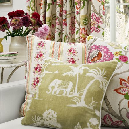 Clarke and Clarke -  Indienne Fabric Collection - Pink, white, grey and green floral curtains and cushions with an olive green elephant and tree print cushion, on a white sofa
