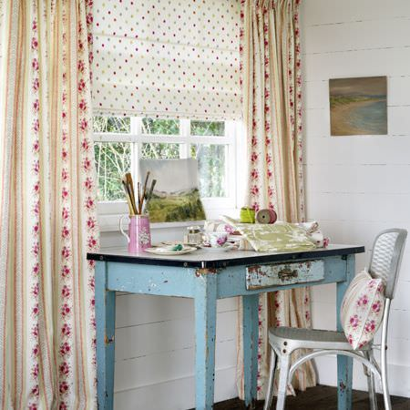 Clarke and Clarke -  Indienne Fabric Collection - Dark pink and white dotted blind with matching floral curtains and cushion, with a silver chair and a distressed blue desk