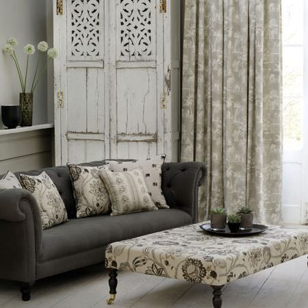 Clarke and Clarke -  Indienne Fabric Collection - Dark and light shades of grey making up a plain sofa, patterned cushions and curtains, and a large padded footstool