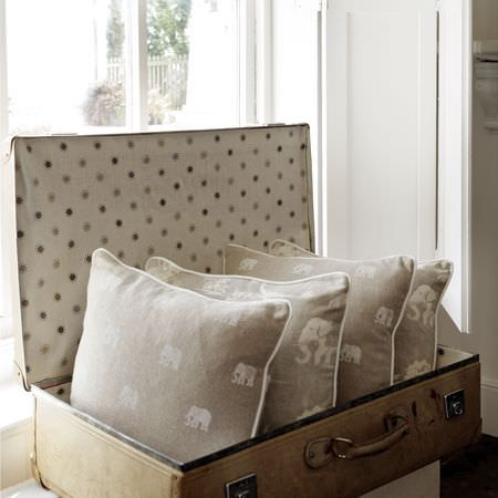 Clarke and Clarke -  Indienne Fabric Collection - Small and large white elephants printed on 4 light grey cushions in a light beige suitcase lined with polka dot fabric