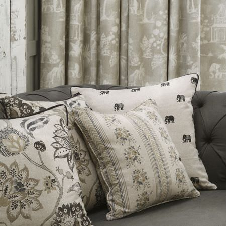 Clarke and Clarke -  Indienne Fabric Collection - Floral, patterned and elephant print cushions and curtains made in white, black and grey shades, on a plain dark grey sofa