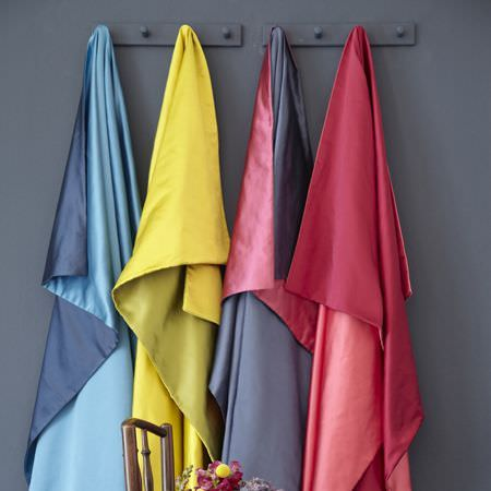 Clarke and Clarke -  Java Fabric Collection - Hanging strips of satin fabric in red, black, yellow and blue in a simple setting