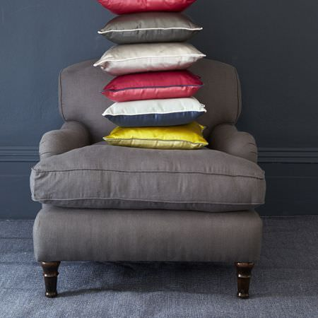 Clarke and Clarke -  Java Fabric Collection - A stack of satin cushions in grey, white, red, yellow and blue in a low key setting