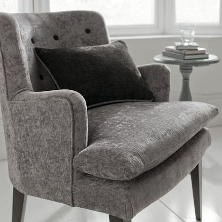 Clarke and Clarke -  Karina Fabric Collection - A stripped back, black and white space with a cushion and chair upholstered in fabric