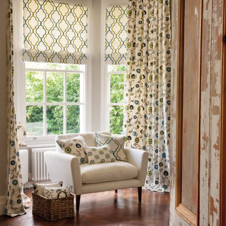 Clarke and Clarke -  Kashmir Fabric Collection - Turquoise and green florals and patterns on white cushions and curtains, on a white armchair beside a wicker basket