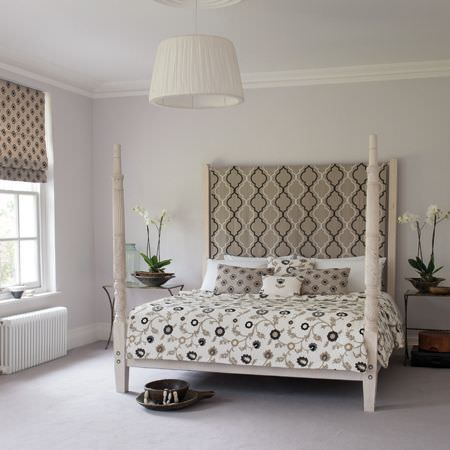 Clarke and Clarke -  Kashmir Fabric Collection - White four-poster bed with a patterned headboard, bedding, cushions and a blind, all in beige, grey, white and black