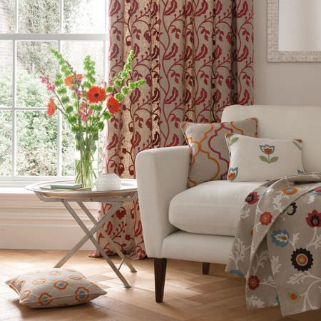 Clarke and Clarke -  Kashmir Fabric Collection - White sofa with red and beige curtains, patterned and floral throws and cushions in white, grey, red and green, with a table