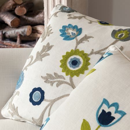 Clarke and Clarke -  Kashmir Fabric Collection - Flocked grass green, light blue, navy and grey simple floral designs on white scatter cushions on a white sofa beside logs