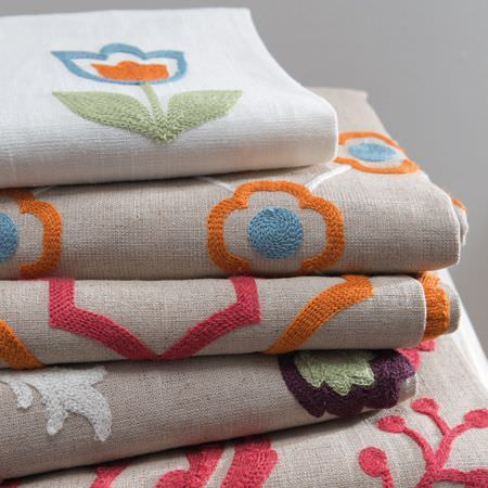Clarke and Clarke -  Kashmir Fabric Collection - Folded white and grey fabrics with floral designs flocked in orange, pink, dark purple, white, mint green and blue colours
