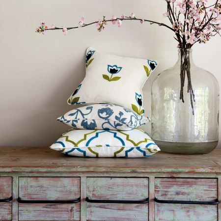 Clarke and Clarke -  Kashmir Fabric Collection - White, blue and green floral and patterned cushions stacked beside a big glass bell jar on a distressed pink-grey dresser