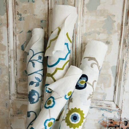 Clarke and Clarke -  Kashmir Fabric Collection - Rolls of white fabric with blue florals, blue and green patterns, and the final two with simple blue, green and grey florals