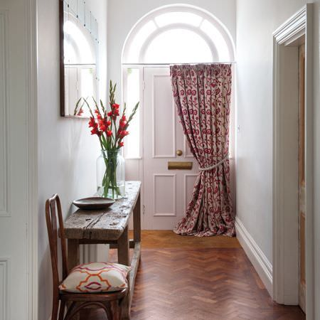 Clarke and Clarke -  Kashmir Fabric Collection - A red and beige floral door curtain tied by a cream cord, with a wooden bench and chair, anda beige, red and orange cushion