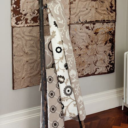 Clarke and Clarke -  Kashmir Fabric Collection - A distressed black A-frame draped with four floral and geometric patterned fabrics inbeige, grey, white and black shades