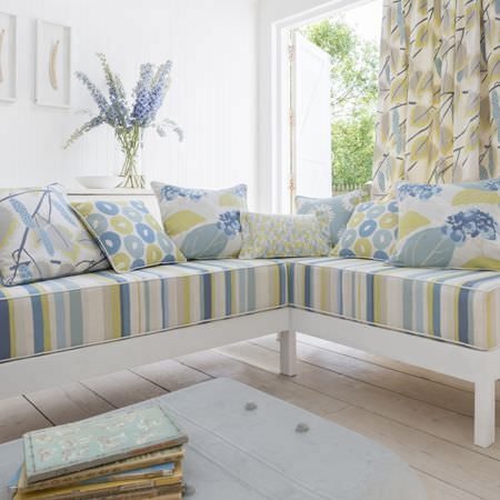 Clarke and Clarke -  La Vie En Rose Fabric Collection - Corner sofa with a white base and a blue, green and white striped seat, with matching patterned cushions and curtains