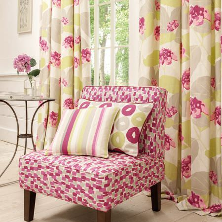 Clarke and Clarke -  La Vie En Rose Fabric Collection - A pink and grey dotted chair with wooden legs, with green, pink, cream and grey cushions and curtains, and a round table