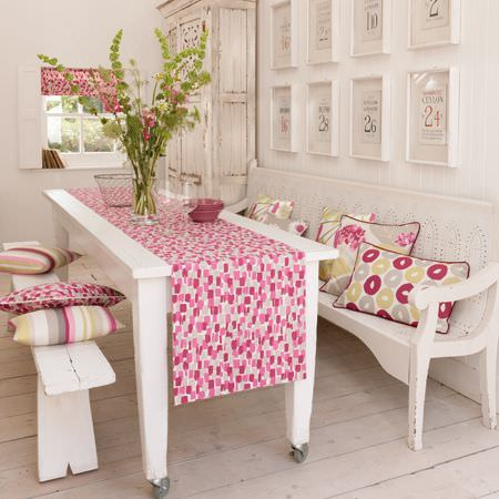 Clarke and Clarke -  La Vie En Rose Fabric Collection - Two different white benches with a white wood table, a pink and grey dotted runner and blind, and patterned scatter cushions