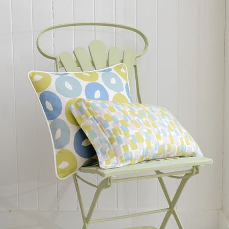Clarke and Clarke -  La Vie En Rose Fabric Collection - A folding chair in pale green with a rectangular and a square cushion, with 2 different green, grey, blue and white patterns