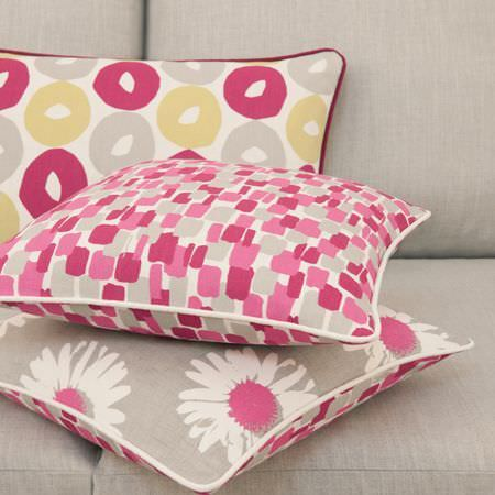 Clarke and Clarke -  La Vie En Rose Fabric Collection - Pink, grey, yellow and white patterned scatter cushions with dots, daisies and circle prints, lying on a light grey sofa