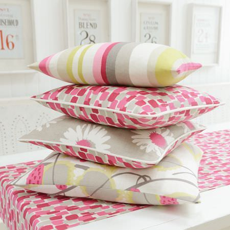 Clarke and Clarke -  La Vie En Rose Fabric Collection - A white table with a pink and grey runner,stacked with four pink, grey, white and yellow cushions with different patterns
