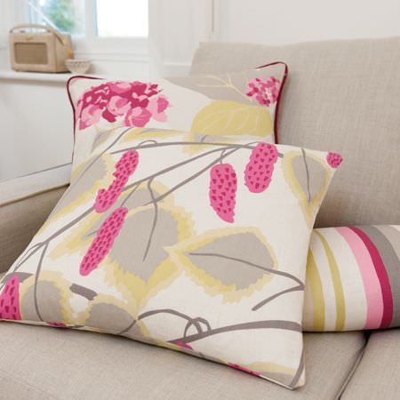 Clarke and Clarke -  La Vie En Rose Fabric Collection - Three pink, grey, white and pale yellow-green floral and striped cushions scattered on a plain light grey coloured sofa