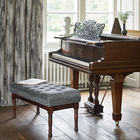 Clarke and Clarke -  Latour Fabric Collection - A grand piano with a large stool upholstered in subtly patterned silver-grey fabric, with grey abstract print curtains