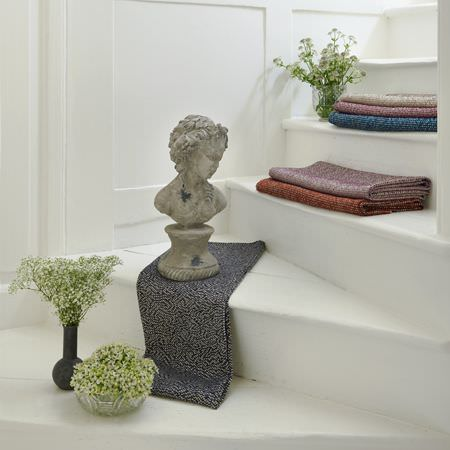 Clarke and Clarke -  Latour Fabric Collection - Subtly patterned grey, red, purple, blue and ivory fabrics placed neatly on stairs, with a classical bust, vases and flowers