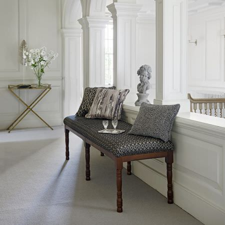 Clarke and Clarke -  Latour Fabric Collection - A black and silver bench seat with wood legs, 3 different grey patterned cushions, a classical bust and a gold folding table
