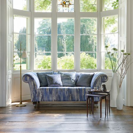 Clarke and Clarke -  Latour Fabric Collection - 2 very large white vases, a nest of 2 wood tables, a gold floor lamp, and a streaky blue and white sofa and cushions