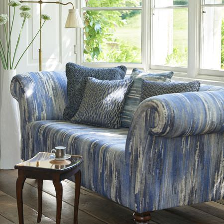 Clarke and Clarke -  Latour Fabric Collection - A sofa covered with streaky blue and white fabric, with matching and patterned cushions, and a small wood and mirrored table