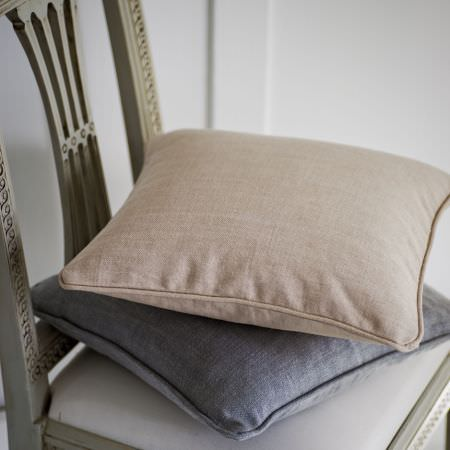 Clarke and Clarke -  Laval Fabric Collection - Two plain beige and dove grey cushions sitting on the pale grey seat of a beautifully carved grey wood chair