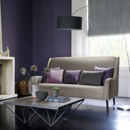 Clarke and Clarke -  Laval Fabric Collection - A grey blind, a large lamp with a black shade, a beige sofa with purple, pink and grey cushions and a modern coffee table