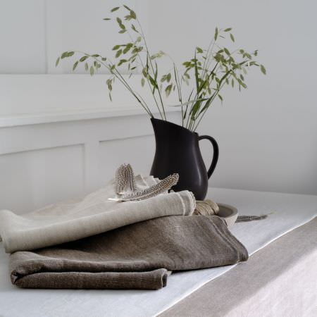 Clarke and Clarke -  Laval Fabric Collection - A white table runner, a black jug, and folds of off-white and dark brown fabric, with a bowl, twine and a feather