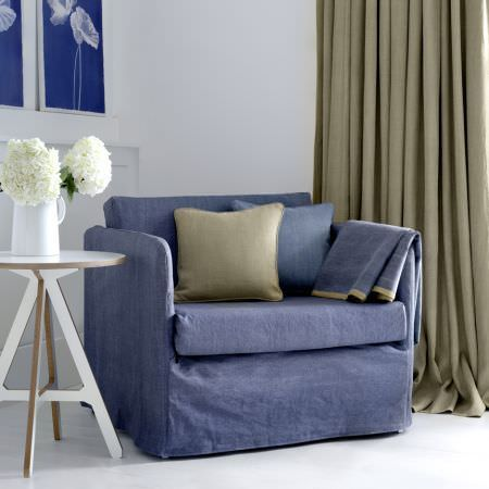 Clarke and Clarke -  Laval Fabric Collection - An armchair covered with denim blue coloured fabric, with cement coloured curtains, 2 matching cushions and a white table