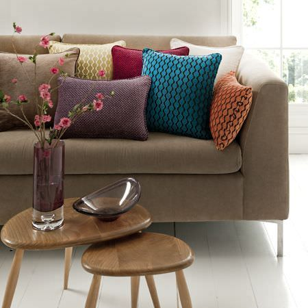 Clarke and Clarke -  Lazzaro Fabric Collection - Blue, orange and brown patterned cushions on a neutral sofa