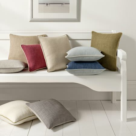 Clarke and Clarke -  Linoso Fabric Collection - White, brown, red and blue cushions of linen on a wooden bench in a clean, simple interior