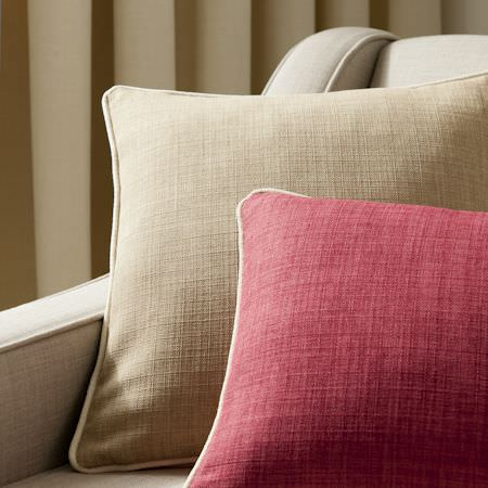 Clarke and Clarke -  Linoso Fabric Collection - Detail of a linen, used on cushions in colours of sandy brown and red in a laid back setting
