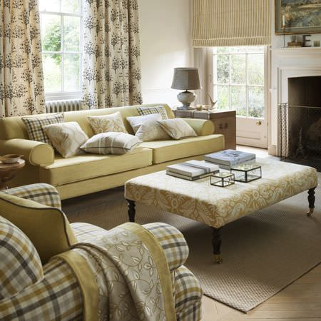 Clarke and Clarke -  Manor House Fabric Collection - A pale yellow sofa, a checked armchair, a large patterned footstool, matching cushions, curtains and blinds, and a grey lamp