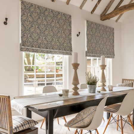 Clarke and Clarke -  Manor House Fabric Collection - A dark table with white chairs, patterned, striped and checked cushions, patterned blinds and large candlestick holders