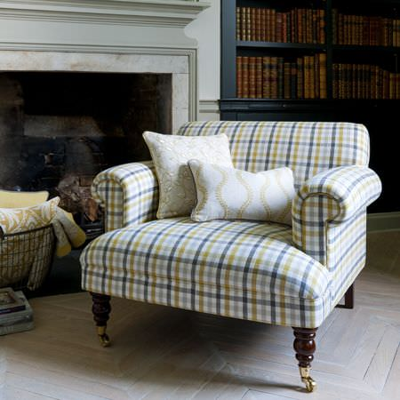 Clarke and Clarke -  Manor House Fabric Collection - A low green, white and grey checked armchair with wooden legs, two white patterned scatter cushions and a mesh basket