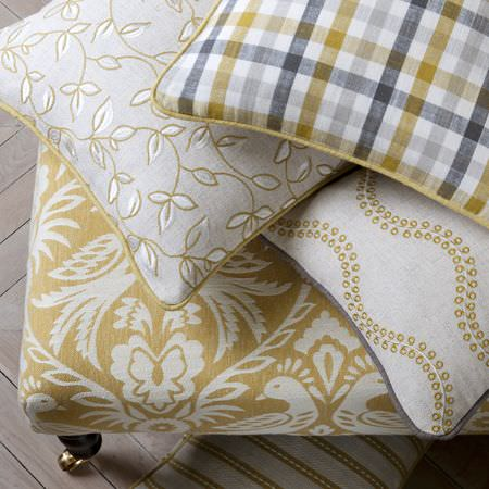 Clarke and Clarke -  Manor House Fabric Collection - Checked, patterned and leaf print cushions on a padded patterned chair, all in white, light green-gold and shades of grey