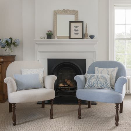 Clarke and Clarke -  Manor House Fabric Collection - A white armchair and a pale blue armchair, both with long wooden legs, with plain and patterned white and blue cushions