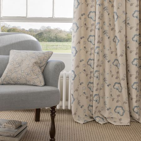 Clarke and Clarke -  Manor House Fabric Collection - Pale blue and grey florals printed on white curtains and a matching cushion, with a pale blue sofa with long wooden legs