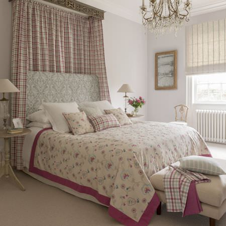 Clarke and Clarke -  Manor House Fabric Collection - A floral throw and cushions on a bed with white bedding, a grey and white headboard, a checked curtain, and a striped blind