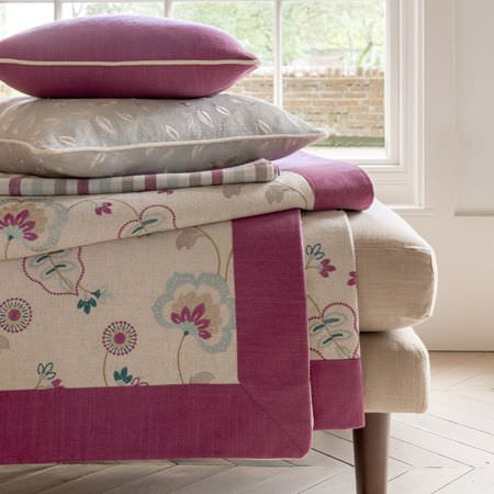 Clarke and Clarke -  Manor House Fabric Collection - A cream footstool with a floral throw edged in fuschia fabric, with a patterned grey cushion and a plain fuschia cushion