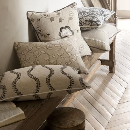 Clarke and Clarke -  Manor House Fabric Collection - A wooden bench loaded with scatter cushions featuring different patterns in cream, beige, grey and black shades
