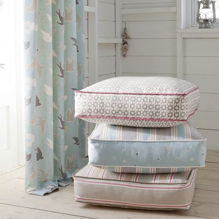 Clarke and Clarke -  Maritime Prints Fabric Collection - Pale blue bird patterned curtain and various patterned seat cushions