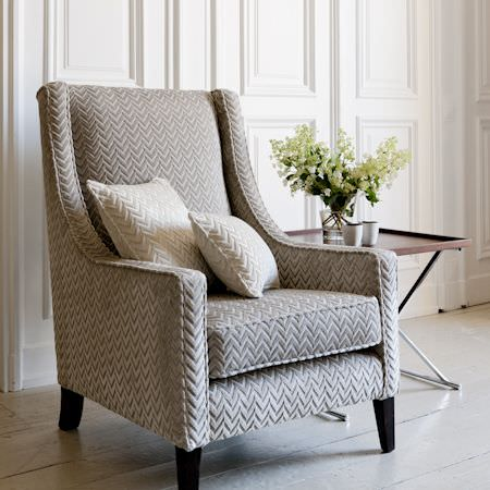 Clarke and Clarke -  Metro Velvets Fabric Collection - An armchair upholstered in grey, herringbone fabric with white cushions, in a spacious, wooden interior