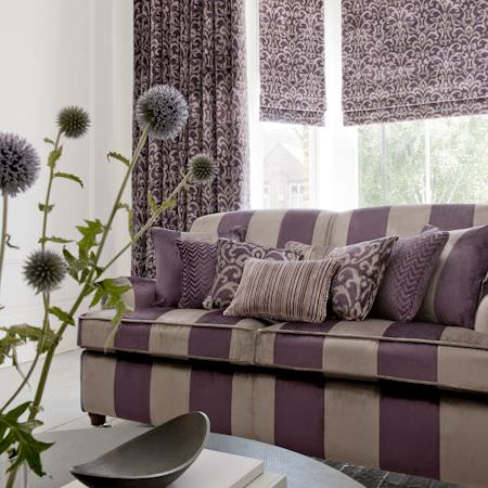Clarke and Clarke -  Metro Velvets Fabric Collection - Striped, herringbone and more ornately patterend styles of fabric adorn a purple and gold sofa, with complimentary roman blinds